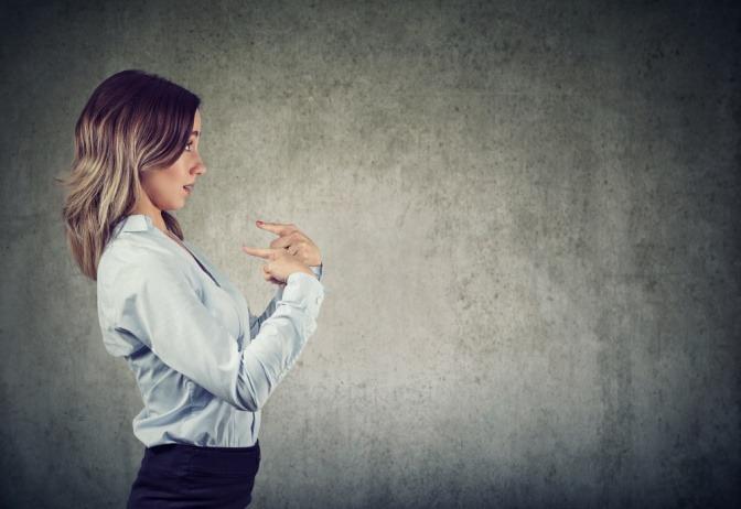 Eine überrascht wirkende Frau, die sich selbst Vorwürfe macht und mit den Fingern auf sich zeigt.