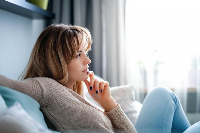 Eine Frau sitzt zuhause auf ihrer Couch und denkt daran, wie sie ihre Zukunft gestalten kann.