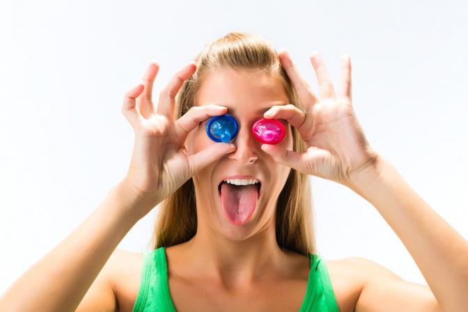eine Frau hält Verhütung ohne Hormone vor die Augen (Kondome) und streckt frech die Zunge raus