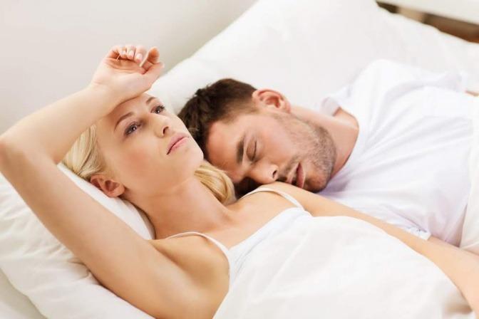 paar im Bett, mann schläft, Frau denkt nach.