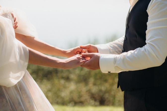 Ein Paar hält Händchen miteinander