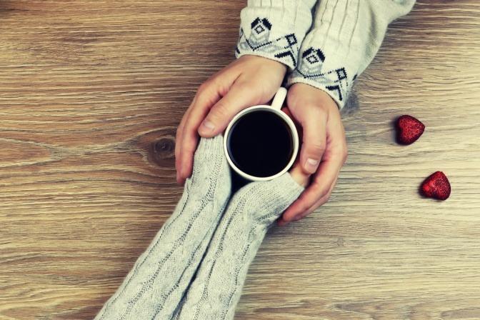 Vier Hände halten eine Tasse und lernen verzeihen