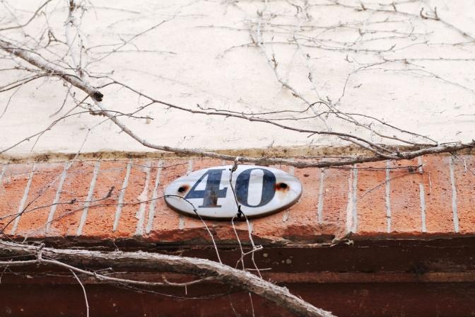 Hausschild mit der Nr. Vierzig auf Ziegelmauer