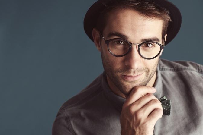 Ein junger Mann trägt eine schwarze Brille