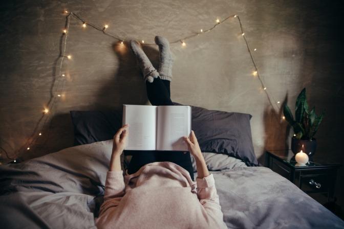 Frau bei Vollmond mit Buch im Bett