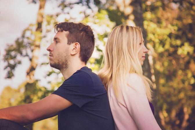 Ein Paar sitzt Rücken an Rücken auf einer Wiese.