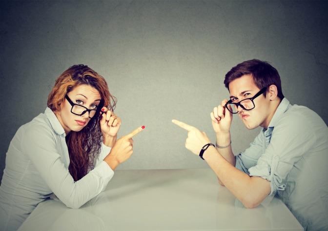 Ein Paar sitzt am Tisch, beide zeigen mit dem Finger auf ihr Gegenüber. Es geht um Vorwürfe, Beziehung und ähnliches.