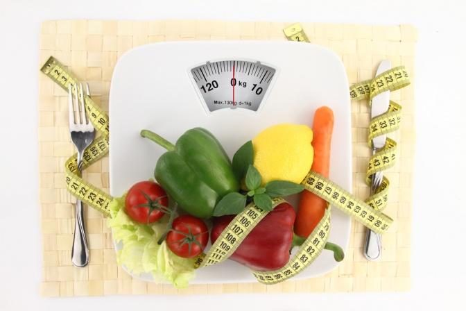Auf einer Waage liegt Gemüse und ein Maßband, daneben Besteck