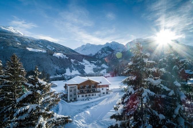 Ein Hotel inmitten einer verschneiten Berglandschaft. Hier kannst du natürlich auch wandern, Winter ist hier gleichbedeutend mit kalter Sommer.
