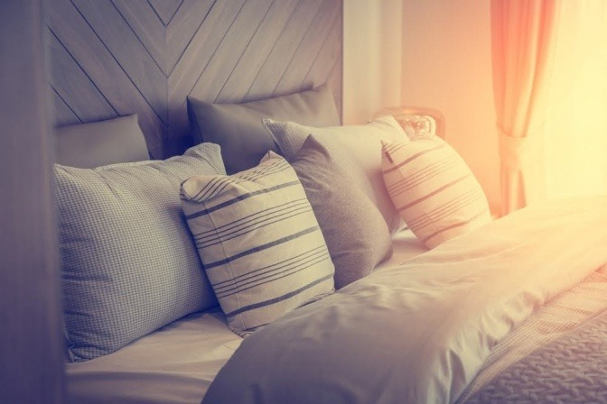Ein kuschelig und einladend wirkendes Bett wird von einer sanften Abendsonne bestrahlt.