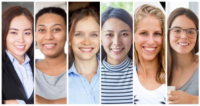 Frauen mit diversen Ethnien nebeneinander gestellt, sie lächeln in die Kamera.
