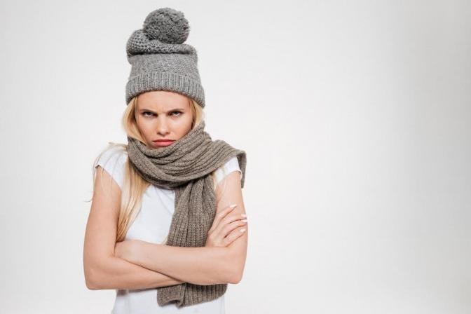Eine Frau mit verschränkten Armen und einem grimmigen Gesichtsausdruck blickt in die Kamera. Sie würde bestimmt gerne wissen: Was hilft gegen schlechte Laune?