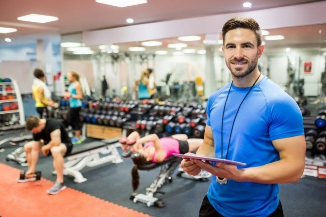 Ein Fitnesstrainer steht zwischen Sportlern in einem Fitnessstudio und hält ein Klemmbrett in der Hand.