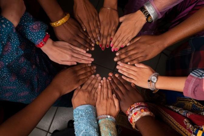Mehrere Personen unterschiedlicher Nationalitäten oder Hautfarben bilden mit ihren Händen einen Kreis.