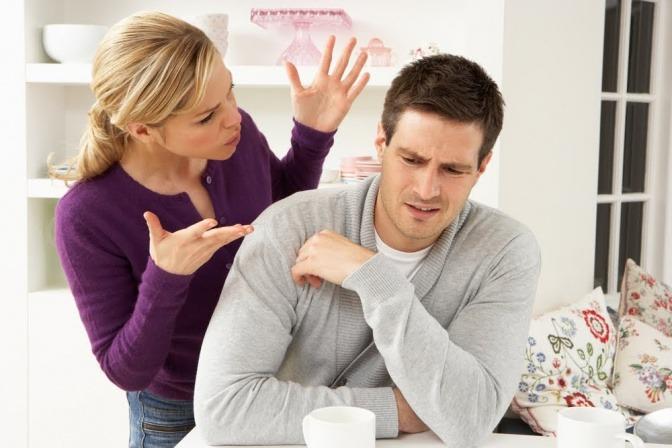 """Ein Paar streitet sich, vielleicht über die Frage """"Was tun gegen Eifersucht?"""". Sie gestikuliert wild mit den Händen, während er resigniert am Tisch sitzt."""