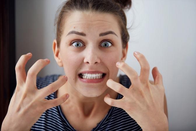 Eine wütende Frau, die sich von etwas gestört fühlt.