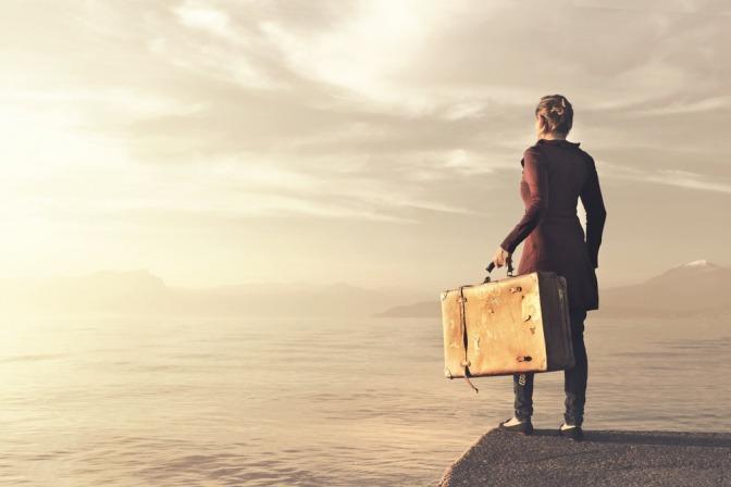 Eine Frau steht mit gepackten Koffern bereit, um sich auf die Suche nach dem Sinn des Lebens zu begeben.