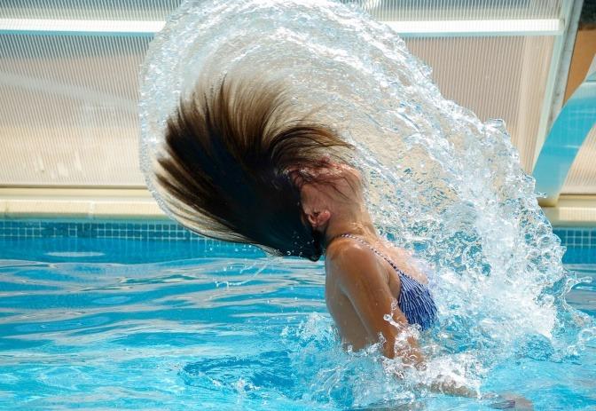 Frau im Swimmingpool taucht aus dem Wasser auf und wirft lange Haare nach hinten