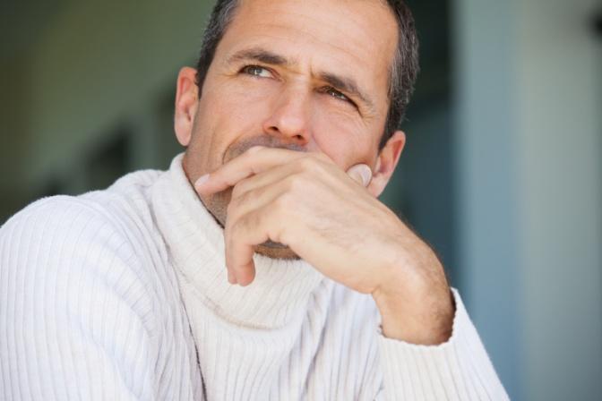 Mann in weißem Pullover schaut nachdenklich in die Ferne