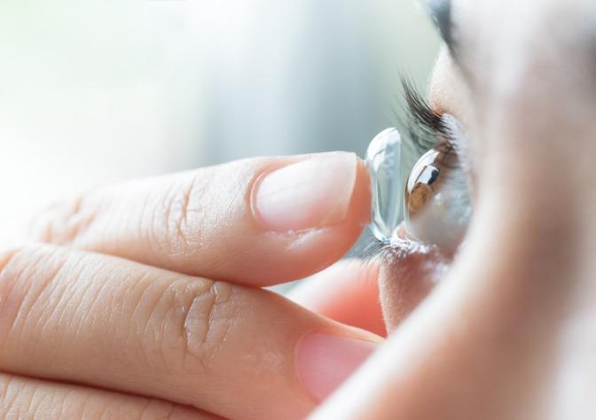 Eine Frau gibt weiche Kontaktlinsen auf das Auge