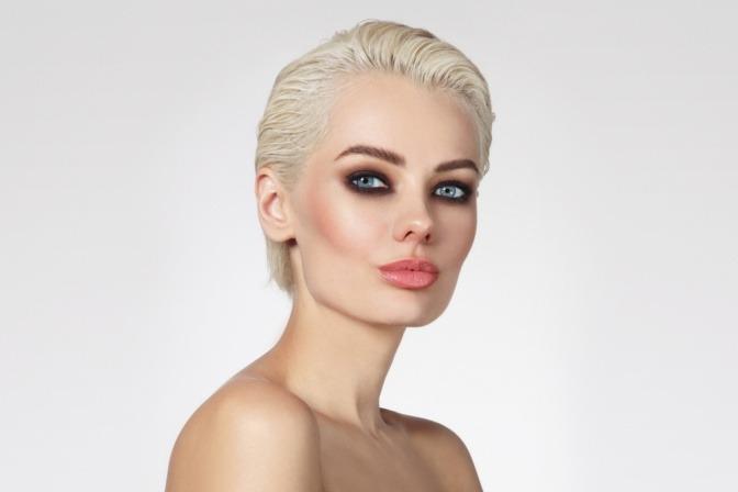 Eine blonde Frau hat ihre kurzen Haare in einem Wet-Look gestylt