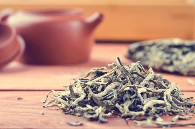 Blätter von weißem Tee liegen neben einer Tasse