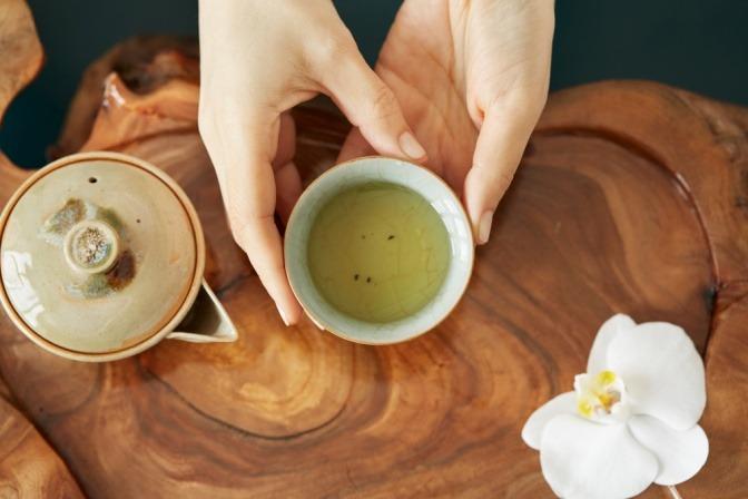 Eine Frau hält eine Tasse mit zubereitetem weißen Tee