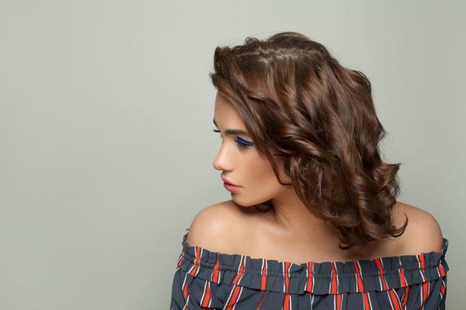 Eine kleine Frau trägt eine Frisur mit Wellen
