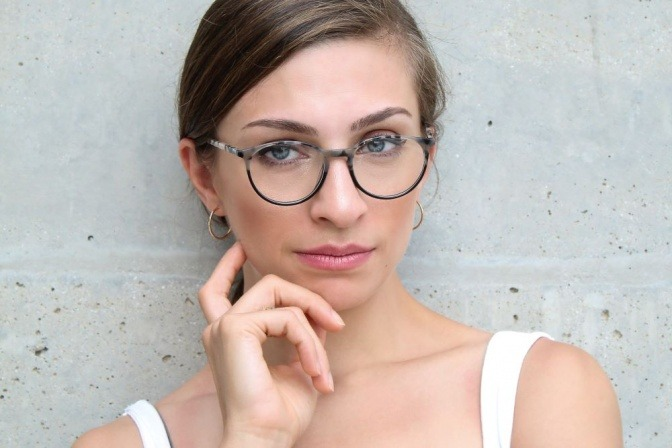 Selbstbewusste Frau mit runder Brille