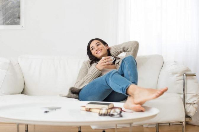 Eine Frau liegt auf einem Sofa und lächelt zufrieden. Sie hält eine Tasse in der Hand.