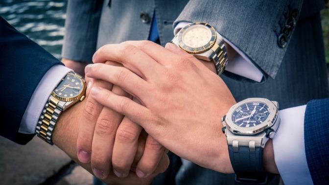 Drei potentielle Geschäftspartner halten ihre Hände mit Uhren aufeinander