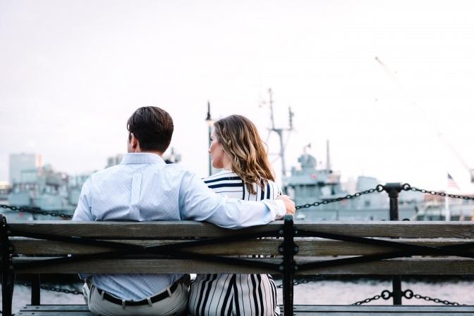 Ein Paar sitzt auf eine Bank in einem Hafen, beide schauen in die gleiche Richtung, wirken jedoch voneinander distanziert.