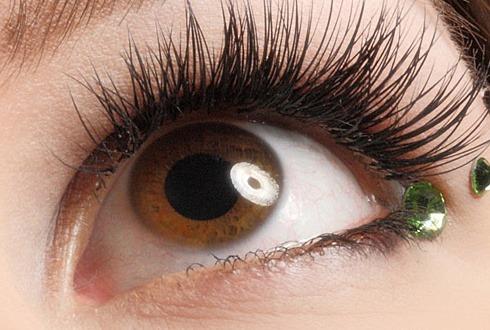 Augen mit verlängerten Wimpern und grünen Strasssteinen