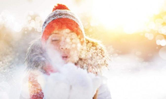 Eine Frau steht draußen im Schnee und pustet eine Wolke mit Pulverschnee von ihren Handflächen.