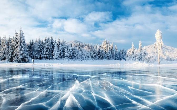 Ein zugefrorener See im Vordergrund, schneebedeckte Nadelbäume im Hintergrund.