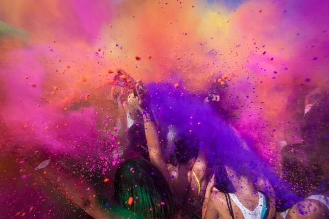 Mehrere Menschen feiern auf einer Straße und besprühen sich dabei mit Farbe.