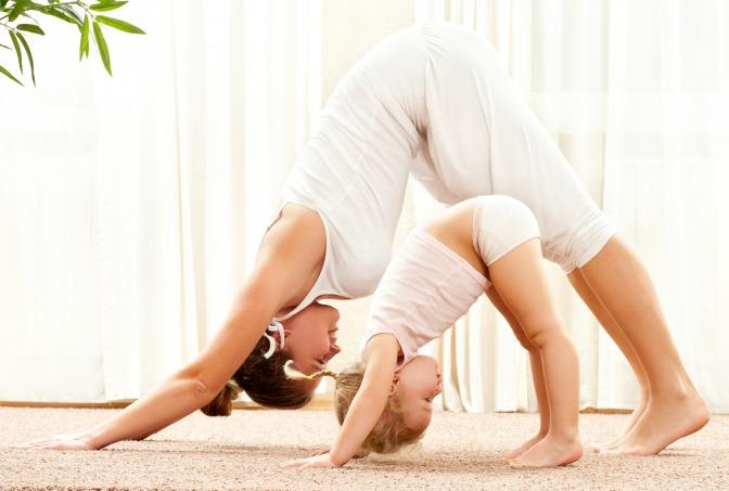 Frau mit kleinem Mädchen beim Yoga.