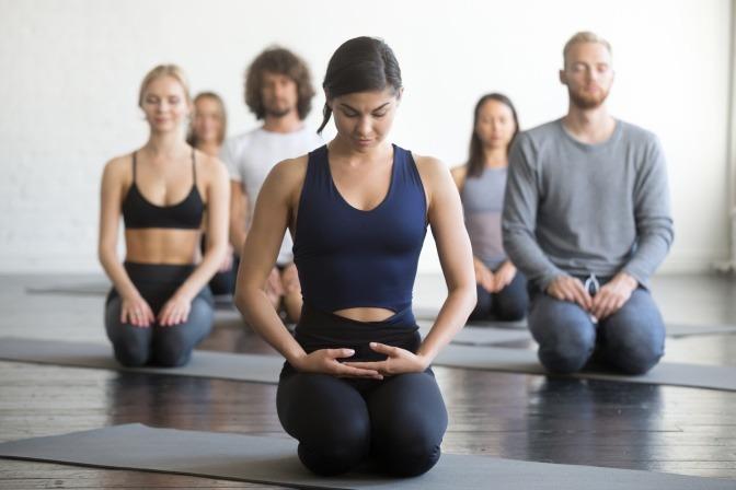 Gruppe junger Menschen beim Yoga.