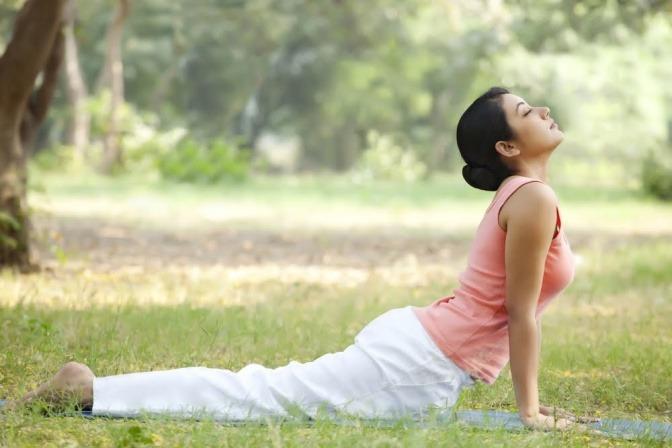 Eine Frau macht Sportübungen in einem Park gegen Mittagstief.