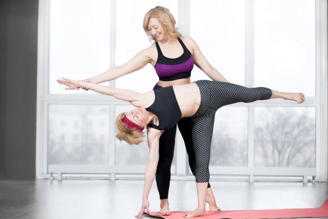 Eine Yogalehrerin übt mit einer Yoga-Schülerin