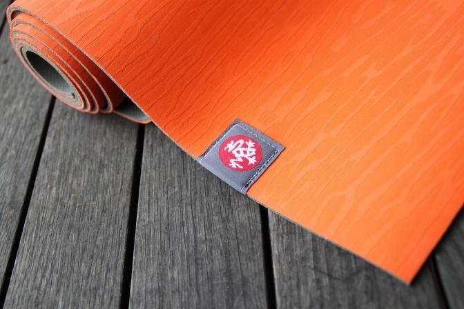 Eine Yoga-Matte liegt eingerollt auf dem Boden