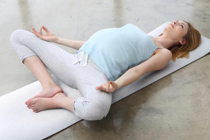 Eine schwangere Frau liegt am Rücken und meditiert