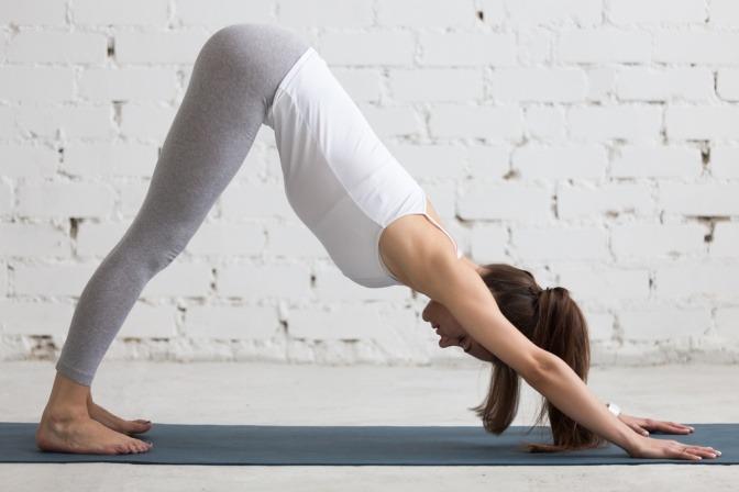 Eine Frau übt die Yoga Übung Hund für einen frischen Teint