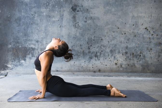 Eine Frau macht die Yogaübung Kobra