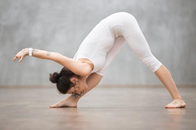 Eine Frau führt die Yogaübung Pyramide aus