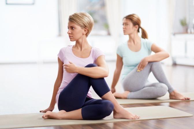 Zwei Frauen führen die Yoga Übung Drehsitz aus