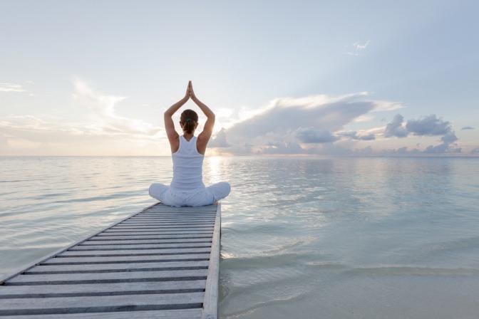 Frau in Yogapose auf einem Steg
