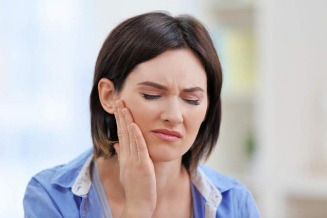 Eine Frau hat Zahnschmerzen und greift auf ihre Backe