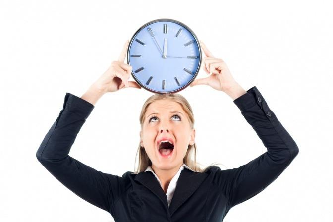 Eine verzweifelt wirkende junge Geschäftsfrau hält eine übergroße Uhr über ihrem Kopf und symbolisiert so Zeitdruck am Arbeitsplatz.