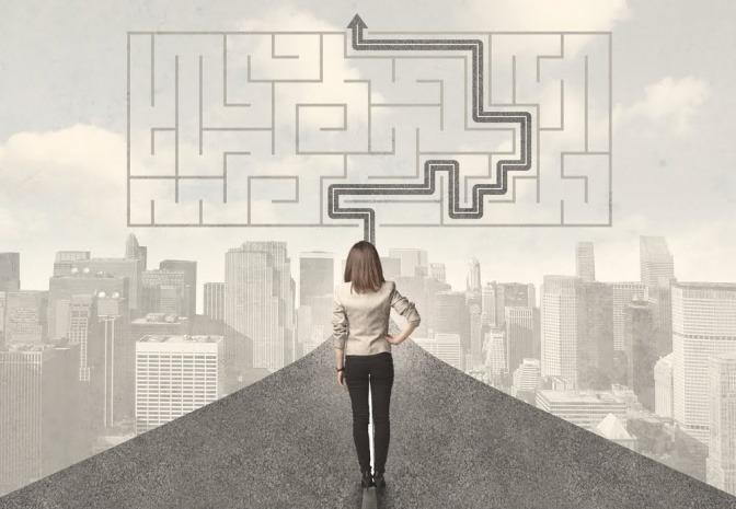 Eine Frau steht auf einem Pfad. Über ihr ist ein Labyrinth, auf dem der richtige Weg zum Ausgang vorgezeichnet ist.